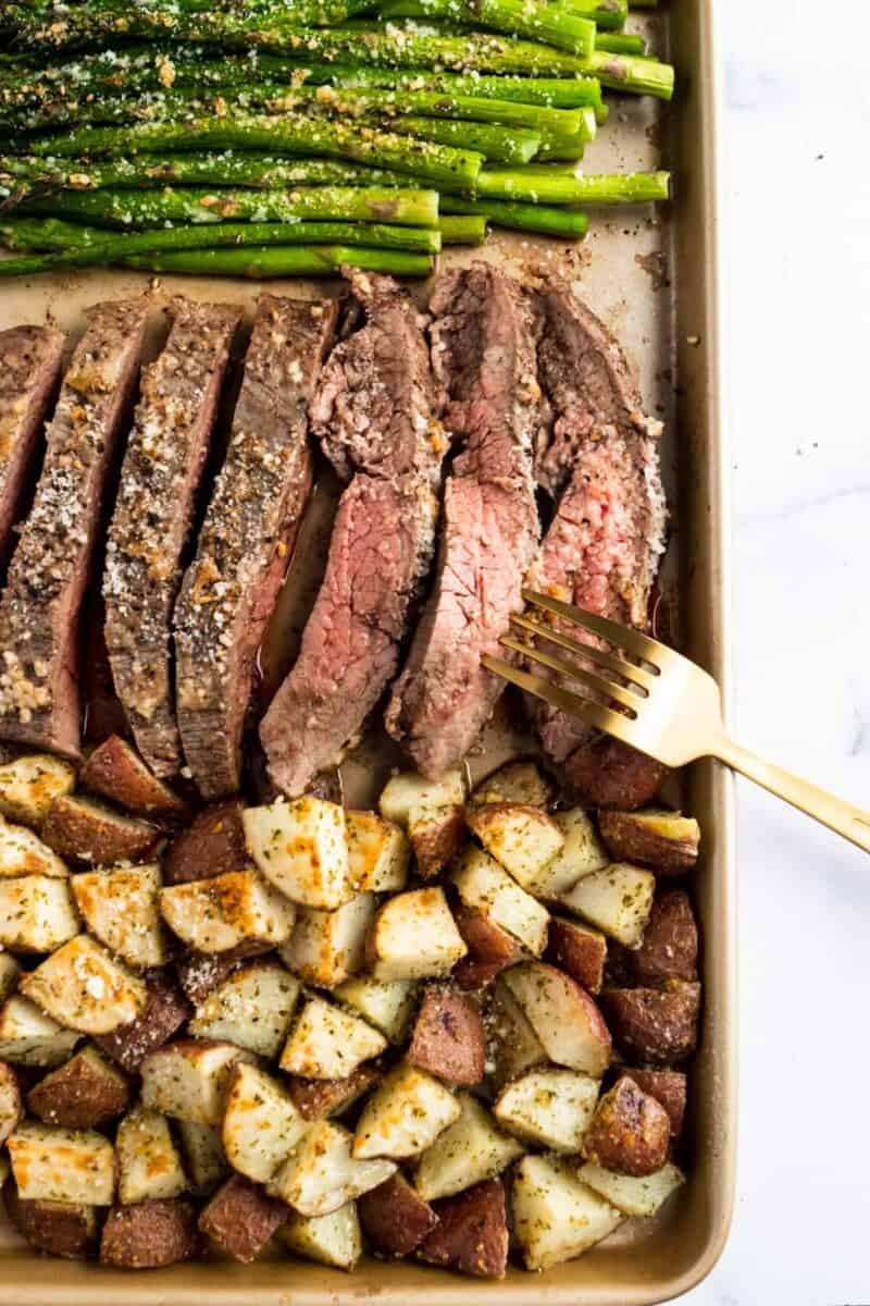Parmesan crusted steak with roasted potatoes and asparagus in a sheet pan
