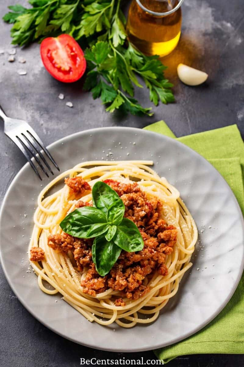 pasta bolognese. Spaghetti with meat sauce. Traditional italian dish served on a gray plate and garnished with basil leaves.