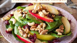 A Thanksgiving Salad Recipes of spinach red and yellow apples cranberries and walnuts. served in a beautiful artisan plate on top of a rustic wooden table.